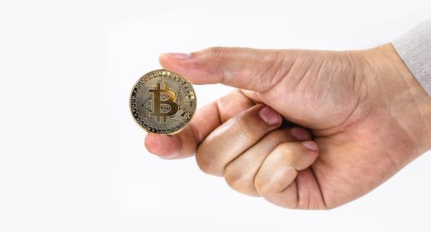 Mâle main tenant une pièce de monnaie bitcoin sur une surface blanche isolée avec copie de l'espace