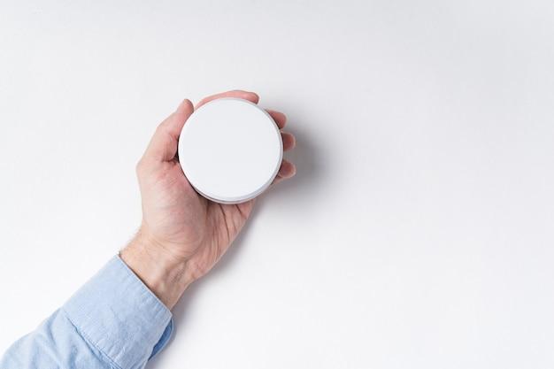 Mâle main tenant un pot cosmétique blanc. maquette sur fond blanc.
