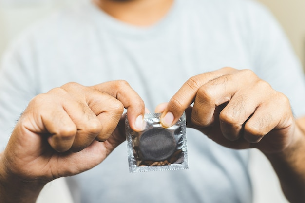Mâle main tenant le préservatif. concept de sécurité sexuelle.