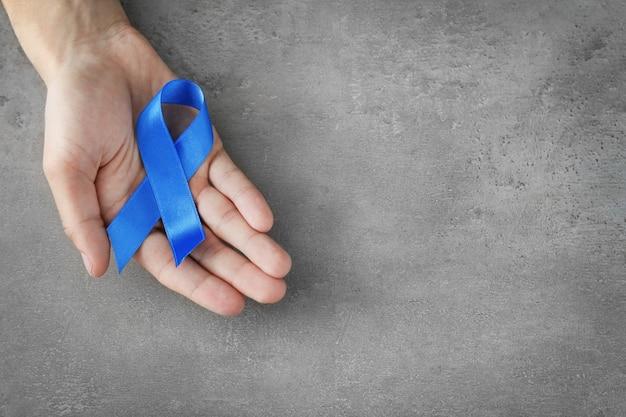 Mâle main tenant un ruban bleu sur fond gris. concept de cancer de la prostate