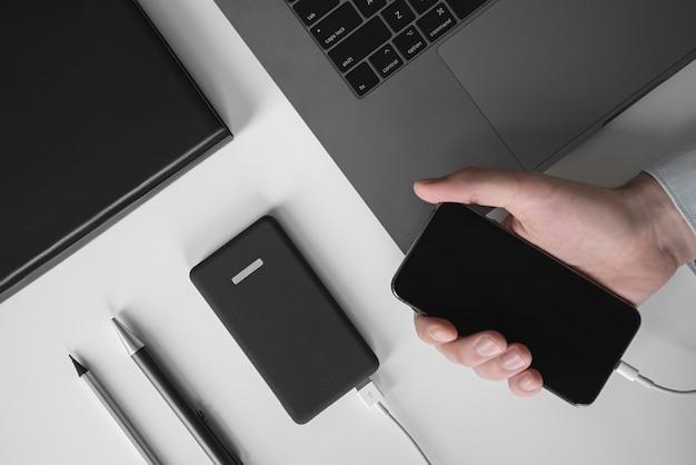 Mâle main tenant le smartphone de charge