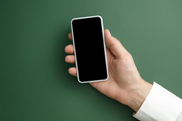 Mâle main tenant le smartphone avec écran vide sur vert