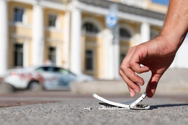 Mâle main tenant un smartphone mobile gravement endommagé après la chute