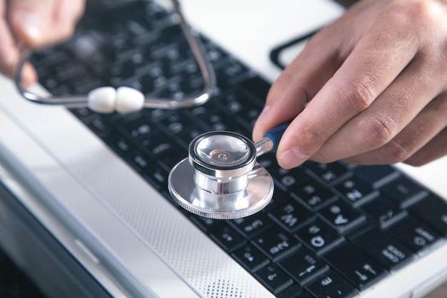 Mâle main tenant un stéthoscope sur un clavier d'ordinateur portable.