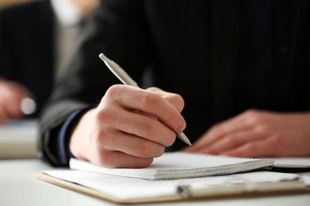 Mâle main tenant un stylo argenté