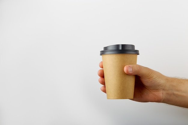 Mâle main tenant une tasse de papier café à emporter isolé sur fond blanc