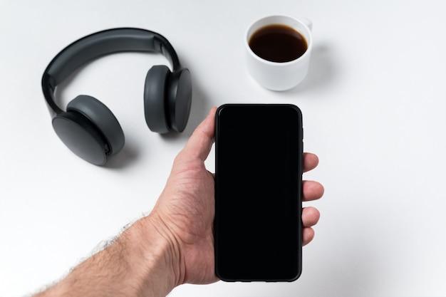 Mâle main tenant le téléphone. casque et café à la surface. espace copie