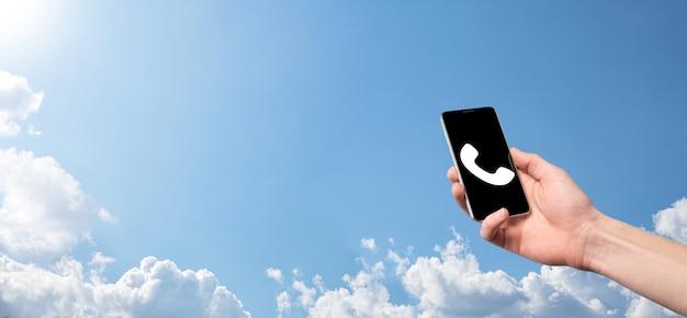 Mâle main tenant un téléphone mobile intelligent avec l'icône du téléphone.appeler maintenant business communication support center customer service technology concept.