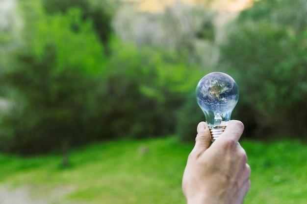 Mâle main tenant la terre dans le bulbe de verre
