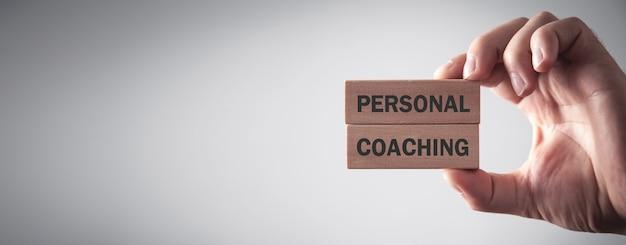 Mâle main tenant le texte de coaching personnel sur des blocs de bois.