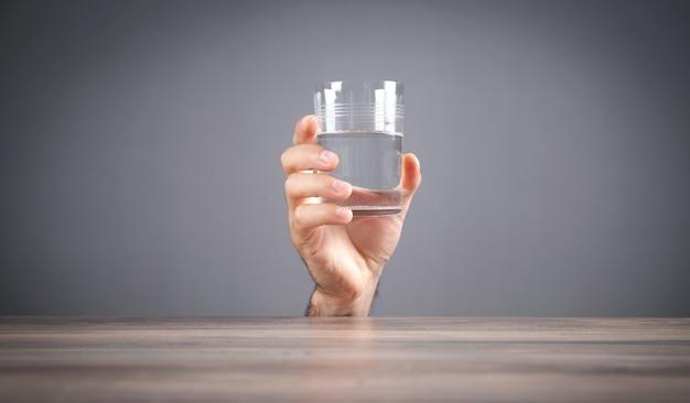 Mâle main tenant un verre d'eau.