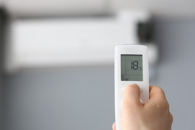 Mâle main tenir la climatisation à distance