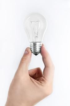 Mâle main tient une ampoule sur fond blanc