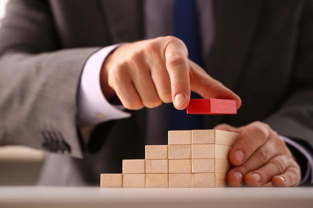 Mâle main tient un bloc d'escalier en bois rouge