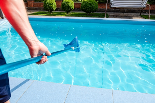 Mâle main tient nettoyeur de filet de piscine