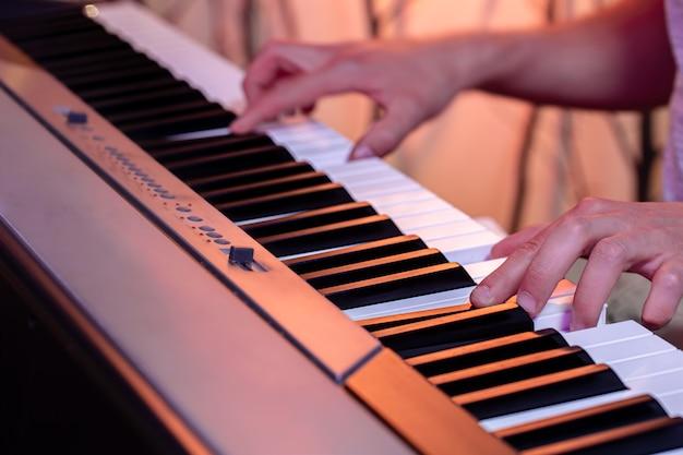 Mâle mains sur les touches d'un piano sur un beau fond coloré se bouchent.