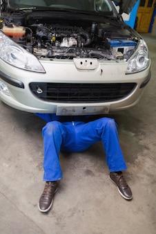 Mâle mécanicien couché sous voiture