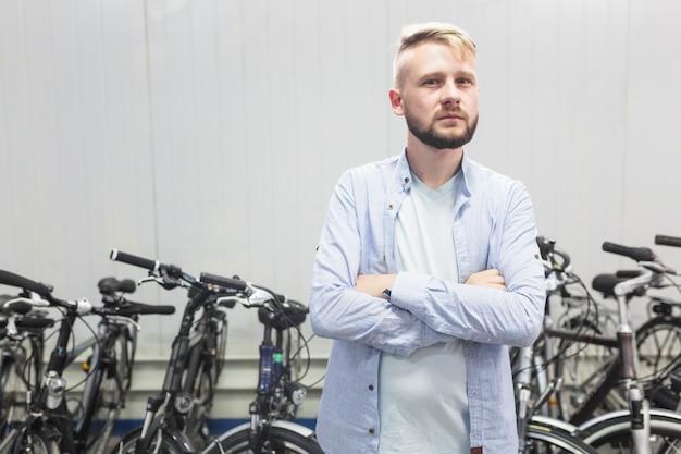 Mâle mécanicien debout devant le vélo