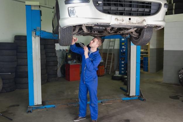 Mâle mécanicien travaillant sous une voiture surélevée dans un garage