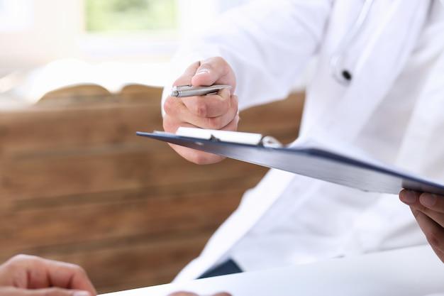 Mâle médecin main tenant un stylo argenté et montrant le tampon.