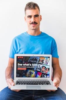 Mâle avec moustache montrant un ordinateur portable avec la page de démarrage de netflix