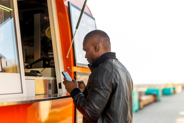 Mâle noir à mi-tir de la commande au camion alimentaire