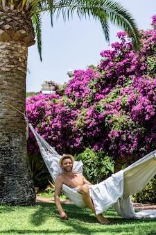 Mâle nu se détendre dans un hamac dans le jardin.