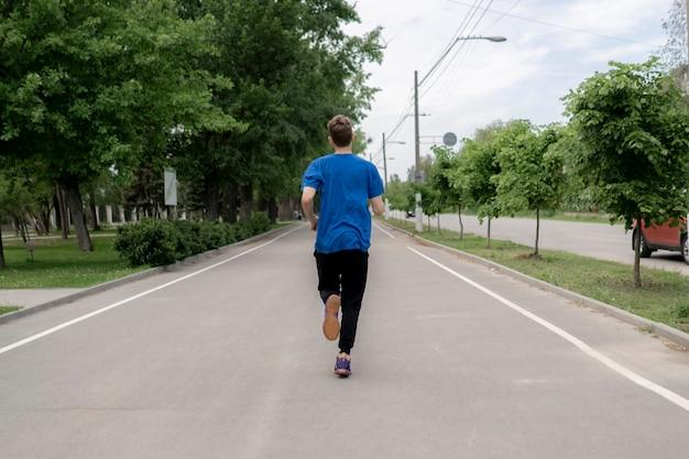Mâle occasionnel masculin faisant courir le matin dans les ruelles de la rue de la ville