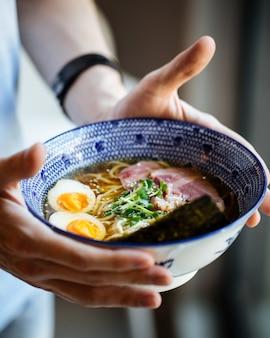 Male's hands holding asiatique japonais shio ramen nouilles soupe aux oeufs