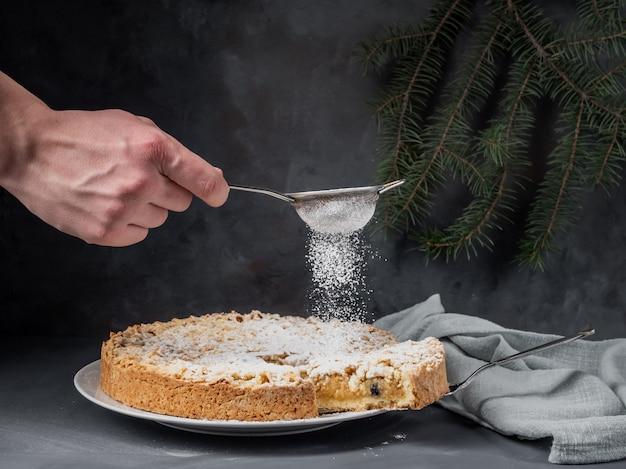 Un mâle saupoudre de sucre en poudre sur une tarte aux pommes, debout sur une table.