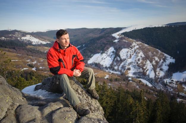 Mâle touriste assis sur un rocher au sommet de la montagne