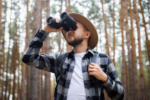 Mâle touriste à la recherche à travers des jumelles dans la forêt.