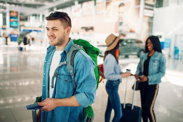 Mâle touriste avec sac à dos détient un passeport à l'aéroport. passagers avec bagages dans l'aérogare, bon voyage, voyage d'été