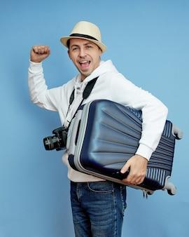 Mâle touriste avec une valise dans ses mains