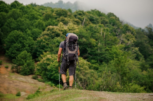 Mâle touristique avec sac à dos se promène dans la vallée