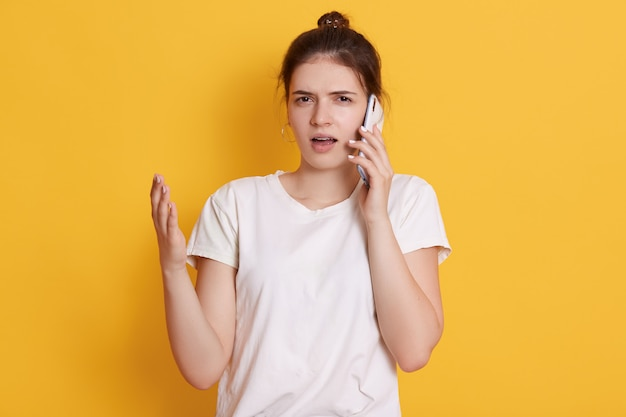Malentendu jeune femme en vêtements décontractés posant contre le mur jaune