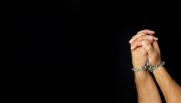 Mâles mains liées chaîne sur fond sombre. concept de dépendance des gens