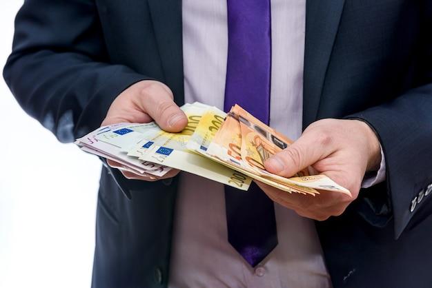 Mâles mains offrant des billets en euros en éventail