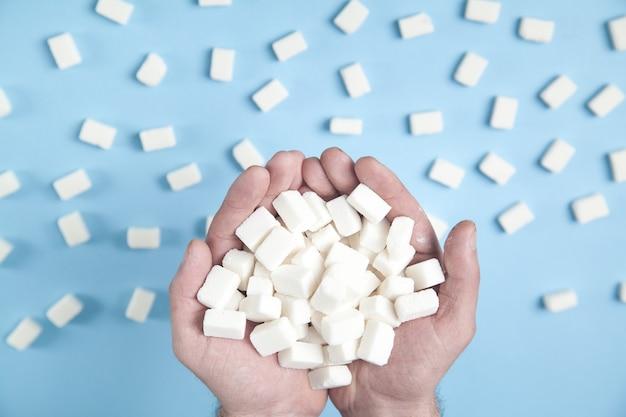 Mâles mains tenant des cubes de sucre sur le fond bleu.