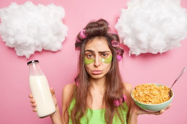 Malheureuse femme brune avec des rouleaux de cheveux sur la tête applique des tampons verts de collagène sous les yeux va prendre un petit-déjeuner sain mange des flocons de maïs avec du lait