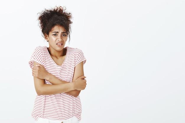 Malheureuse femme avec une coiffure afro qui pose en studio