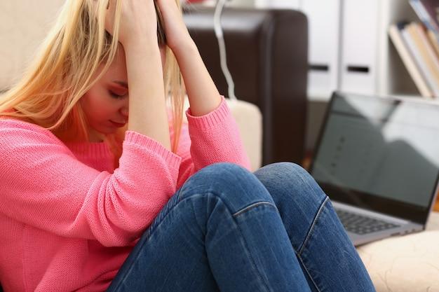 Malheureuse femme déprimée solitaire assise sur le canapé