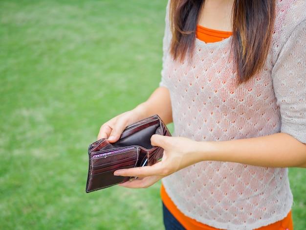 Malheureuse femme en faillite avec portefeuille vide.