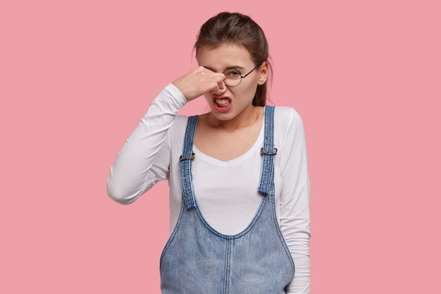 Malheureuse femme insatisfaite fronce les sourcils, tient le nez à cause d'une mauvaise odeur, serre les dents de stinch