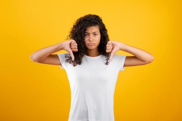 Malheureuse femme noire montrant les pouces vers le bas isolé sur jaune