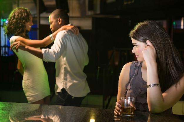 Malheureuse femme regardant un couple qui danse derrière elle au bar