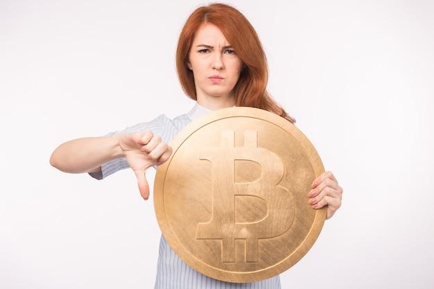 Malheureuse femme rousse tenant un gros bitcoin doré et montrant le pouce vers le bas