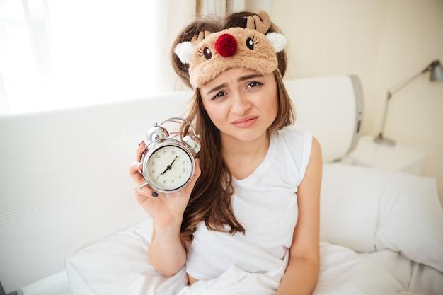 Malheureuse femme tenant un réveil sur le lit