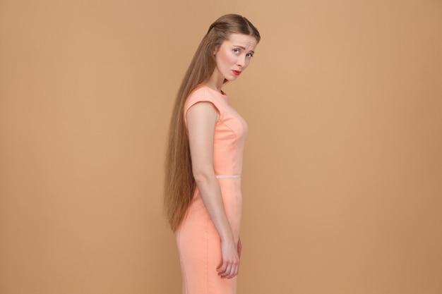 Malheureuse femme triste aux longs cheveux bruns regardant la caméra. émotionnelle mignonne, belle femme avec du maquillage et des cheveux longs en robe rose. intérieur, tourné en studio, isolé sur fond marron clair ou beige.
