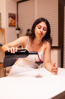 Malheureuse femme versant du vin rouge de la bouteille en verre assis seul à table dans la cuisine. maladie de la personne malheureuse et anxiété se sentant épuisée par des problèmes d'alcoolisme.